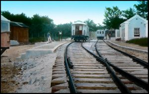 Guy with a bicycle waits by the siding / platform. Nice view of the tracks on what looks like a bed of sand-filled rock.