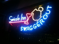 Neon sign behind the bar at The Swizzle Inn over the swizzle machines